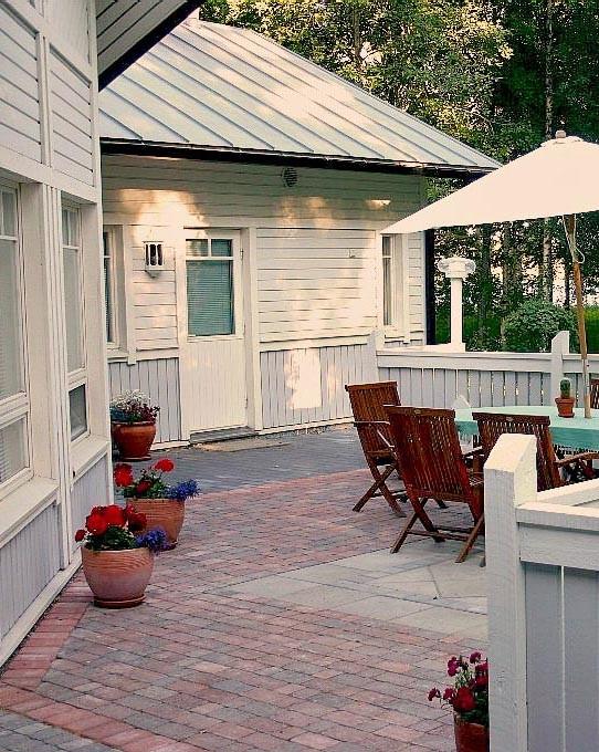 Punamusta kiveys piristää muuten vaaleaa kokonaisuutta  siniharmaan rakennuksen laajalla terassilla.  Värien ohella ( musta, punamusta ja harmaa) pation pinnoitteena on yhdistetty taitavasti betonikiviä ja -laattoja.