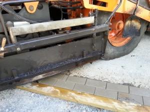 Lankku tukee asfaltin reunaan betonikivistä tehtyä kapeaa rajausta asfaltoinnin ajan.